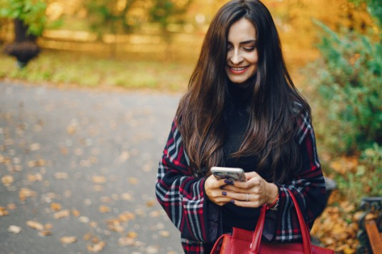 girl-using-her-cell-phone-while-walking-through-the-park-during-autumn_1157-12002